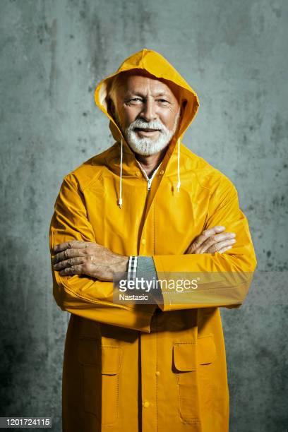 reife mann mit regenmantel mit armen gekreuzt - oberkörperaufnahme stock-fotos und bilder