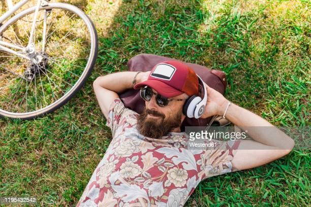 mature man with red basecap, sunglasses and white headphones - hearing protection stock pictures, royalty-free photos & images