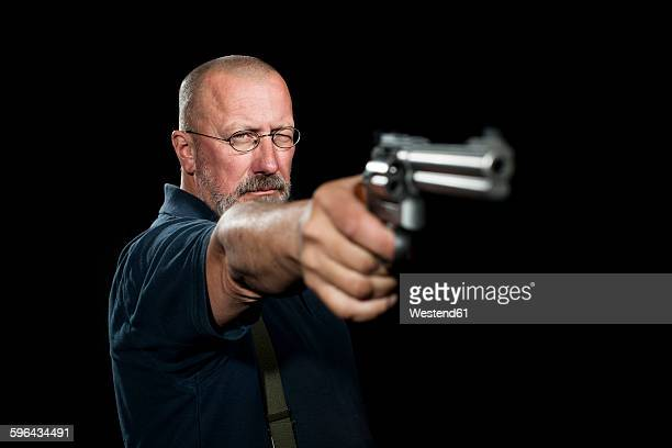Mature man with revolver aiming