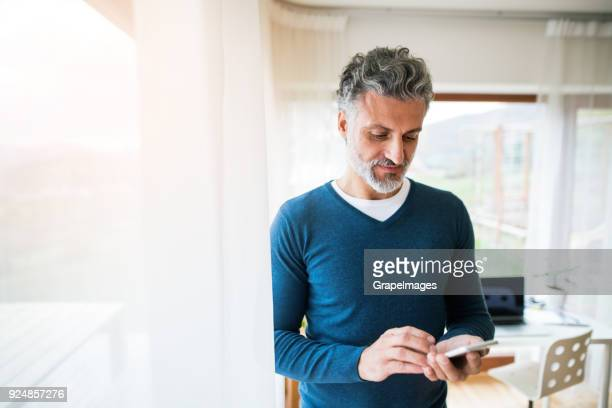 Mature man with smartphone in home office.
