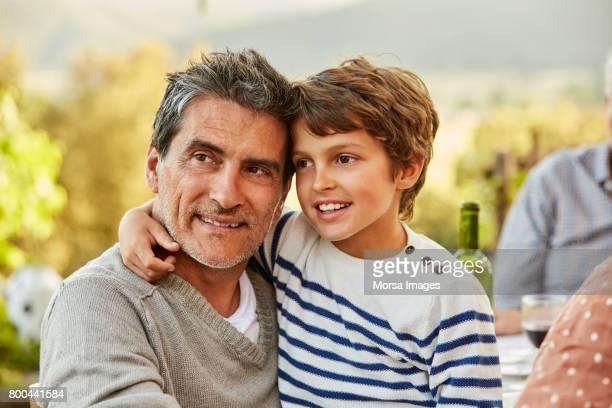 Mature man with son looking away at yard