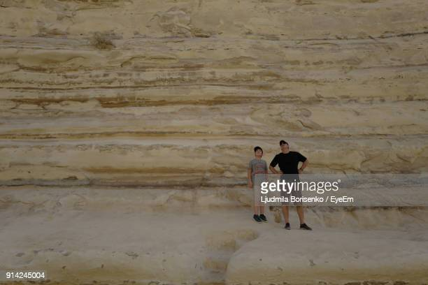 Mature Man With Son Standing Against Rock Formation
