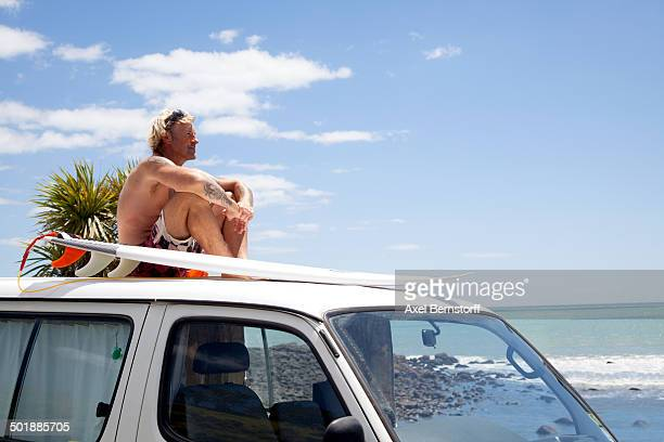 Mature man with surfboard watching from vehicle roof at beach