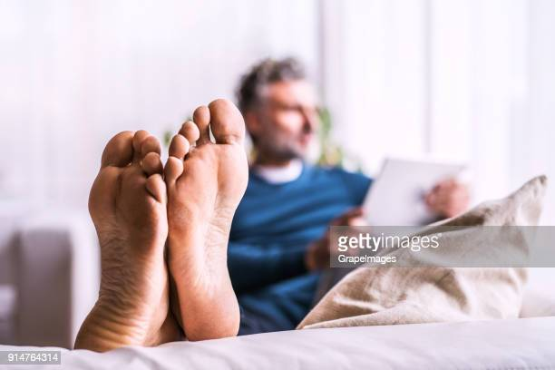 a mature man with tablet at home. - mens bare feet stock photos and pictures