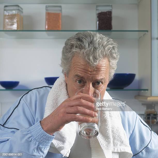 Mature man with towel around neck, drinking glass of water, portrait