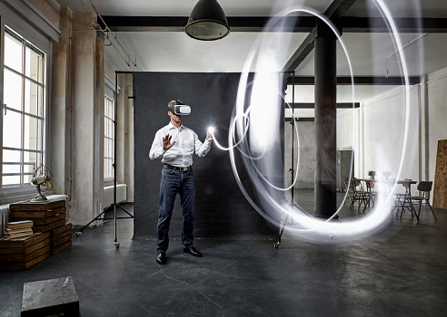 Mature man with vr glasses light painting in front of black backdrop in loft - gettyimageskorea