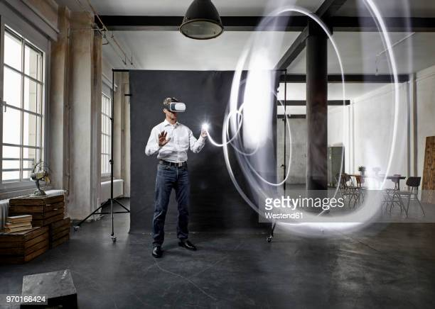mature man with vr glasses light painting in front of black backdrop in loft - realtà aumentata foto e immagini stock