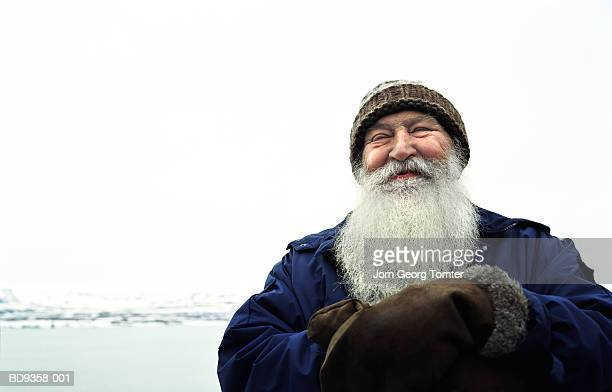 Mature man with white beard smiling, outside, close-up