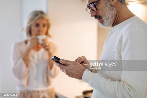 mature man with wife using cell phone in kitchen at home - heterosexual couple stock pictures, royalty-free photos & images