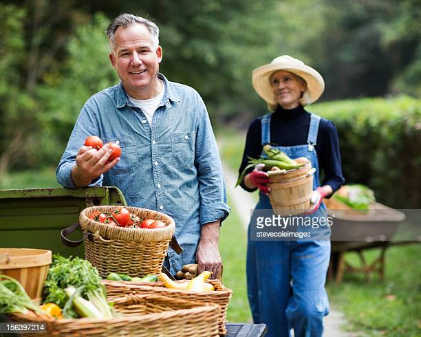 Mature Man With Woman Carrying Basket Of Vegetables.