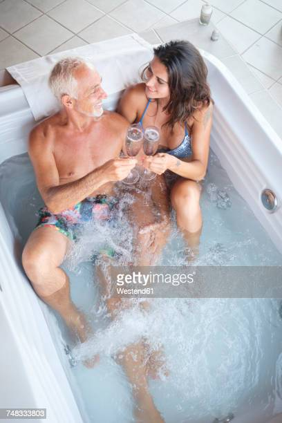 mature man with younger woman enjoying champagne drinks in hot tub hot tub - may december romance stock photos and pictures