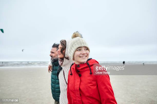 mature man, woman and girl in warm clothing on the beach - schleswig holstein stock pictures, royalty-free photos & images