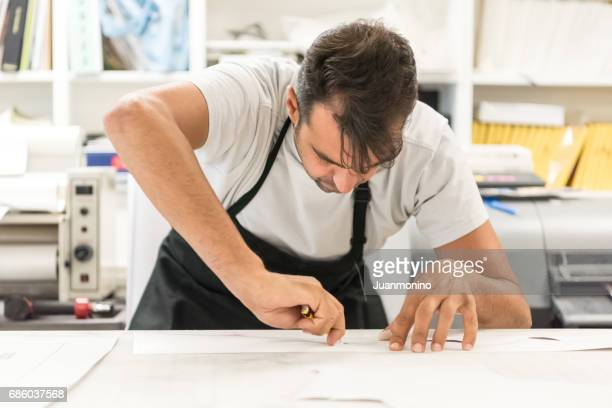 mature man working at his printing-graphic design shop - graphic print stock pictures, royalty-free photos & images