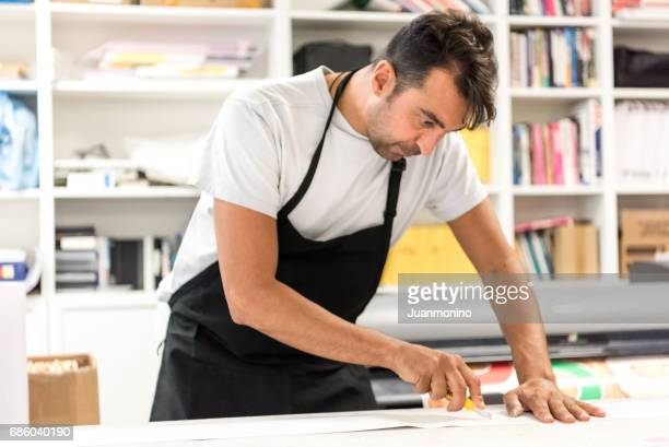 Mature man working at his printing-graphic design shop