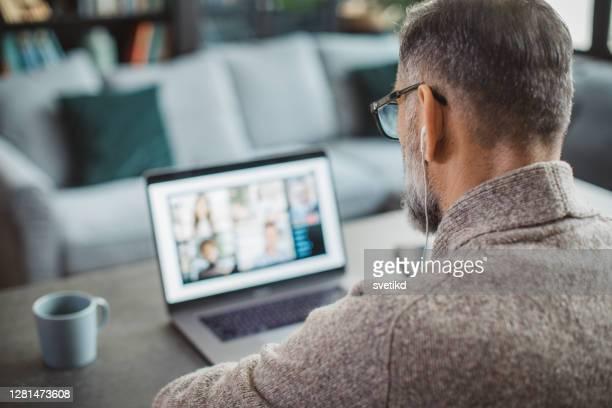 自宅で働く成熟した男 - ウェブ会議 ストックフォトと画像