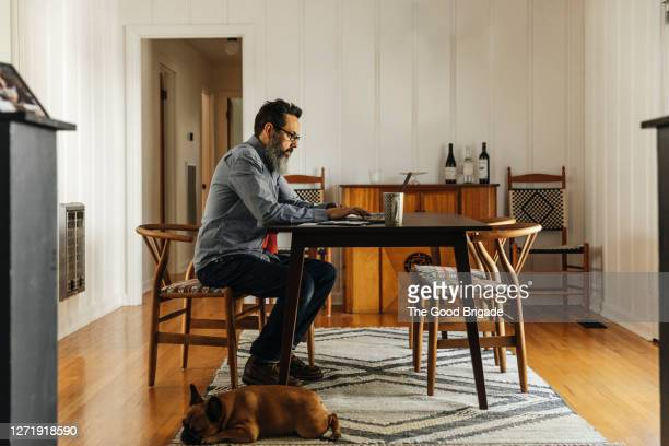 mature man working on laptop in dining room at home - un seul homme photos et images de collection