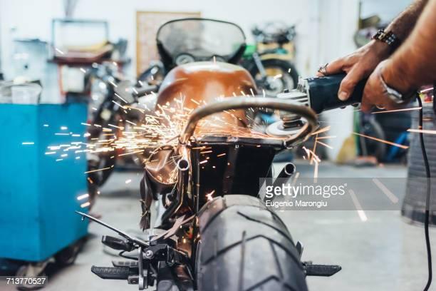 Mature man, working on motorcycle in garage
