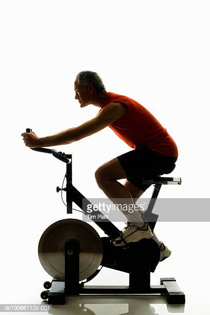 Mature man working out on exercise bike, side view
