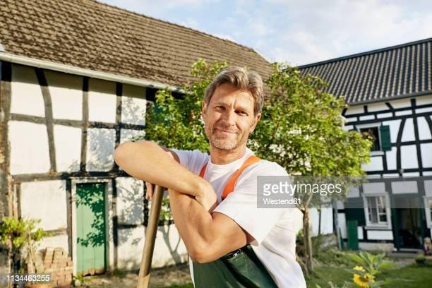 mature man workingin his garden wearing apron - ハーフティンバー様式 ストックフォトと画像