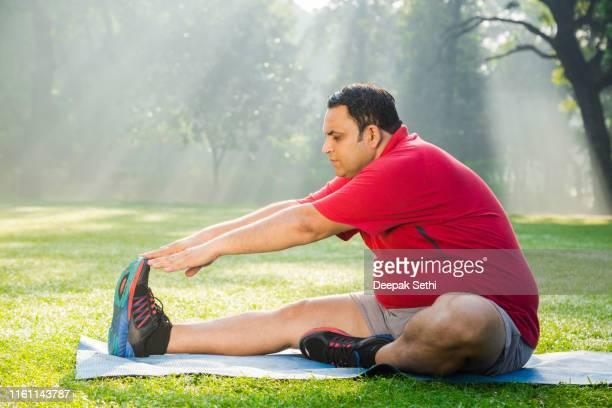 公園で成熟した男のワークアウト - 肥満 ストックフォトと画像