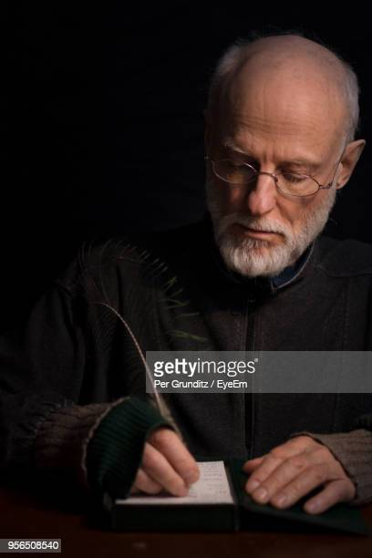 Mature Man Writing In Paper At Table Against Black Background