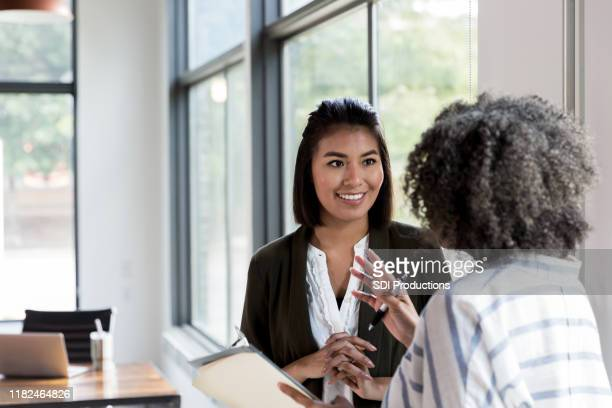 mature manager gives praise to mid adult employee - talking stock pictures, royalty-free photos & images
