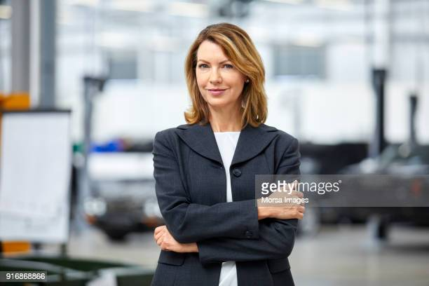 mature manager standing arms crossed in car plant - differential focus stock pictures, royalty-free photos & images