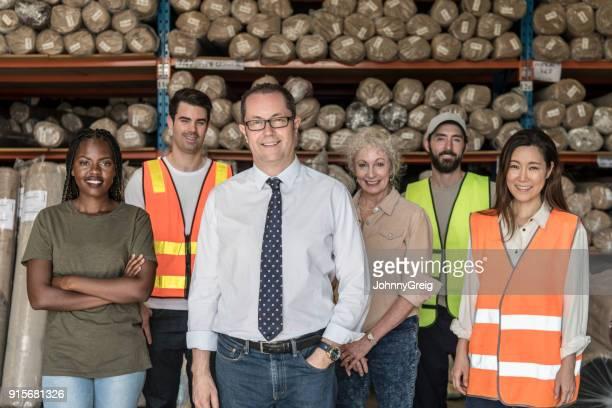 カメラに向かって笑みを浮かべて工場労働者のチームを持つ成熟したマネージャー