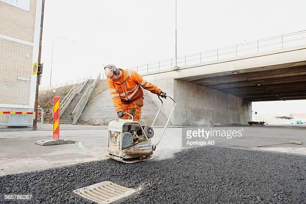 mature manual worker laying asphalt at road construction site - リフレクター ストックフォトと画像