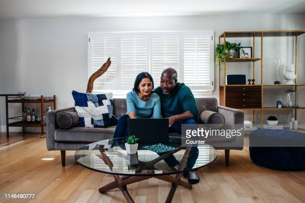 mature married couple at home on the sofa looking at laptop - interracial wife stock pictures, royalty-free photos & images