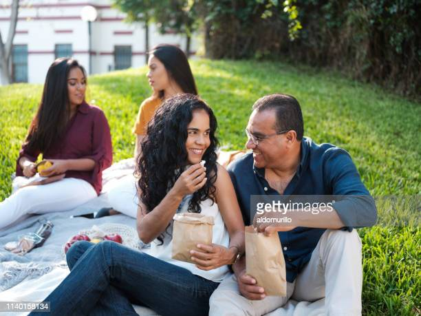 mature married couple smiling at each other and sitting outdoors - mexican picnic stock pictures, royalty-free photos & images