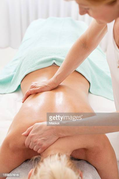 Mature masseur giving a back massage to female customer in health spa