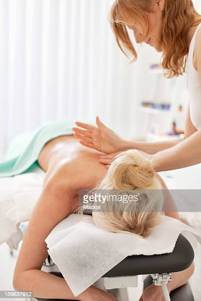 Mature masseur giving back massage to blond female customer in health spa