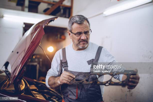 Mature mechanic examining car vehicle part