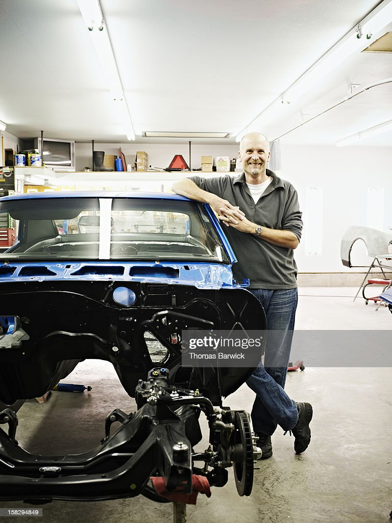 Mature mechanic in garage with car restoration : Stock Photo