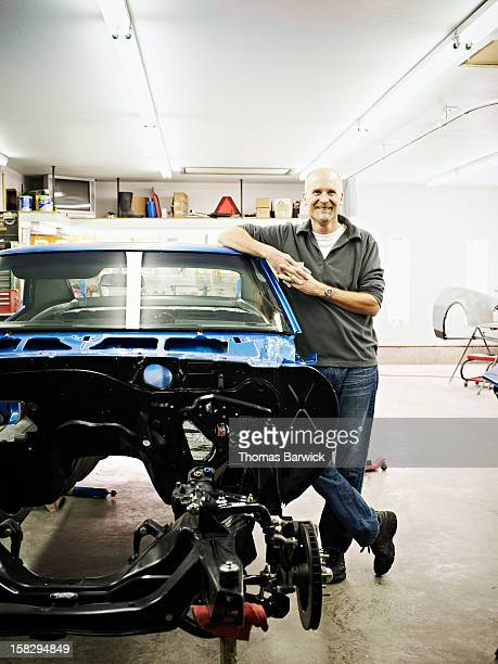 Mature mechanic in garage with car restoration