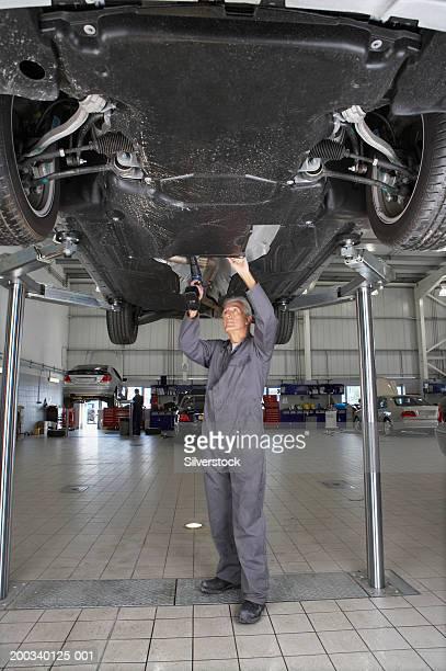 Mature mechanic standing under car in garage using hand drill