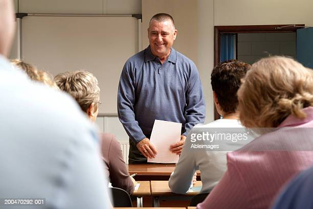 Mature men and women in classroom, teacher standing at front