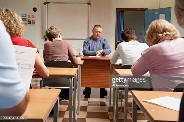 'Mature men and women in examination hall, adjudicator checking watch'