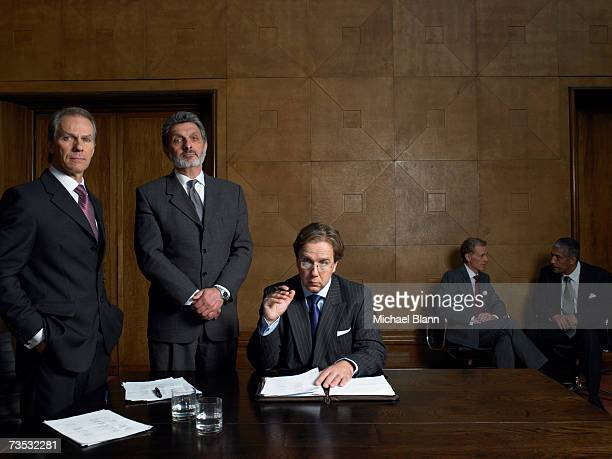 mature men at end of table in conference room, portrait - politik stock-fotos und bilder