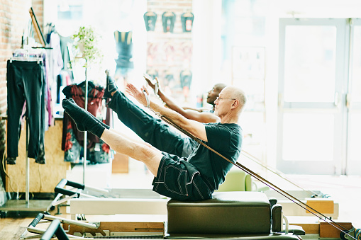 Mature men doing teasers on pilates reformer long box during class in fitness studio - gettyimageskorea