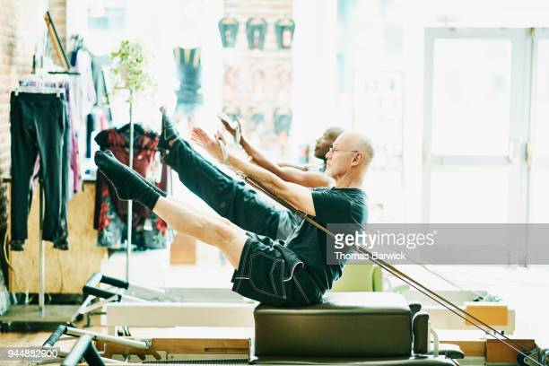 Mature men doing teasers on pilates reformer long box during class in fitness studio