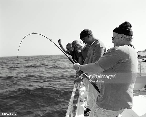 mature men fishing on boat, man holding rod (b&w) - big game fishing stock photos and pictures