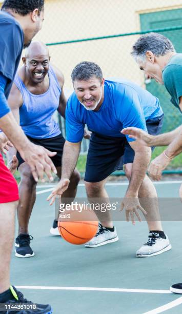 hommes matures ayant l'amusement jouant au basket-ball - combat sport photos et images de collection