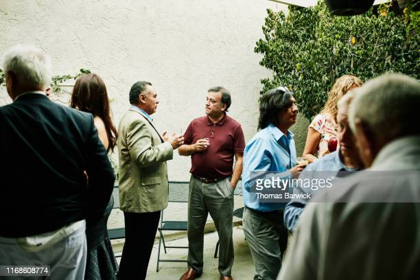 mature men in discussion during cocktail party - cocktail party stock pictures, royalty-free photos & images