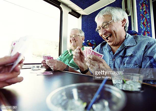 Mature men playing cards on tour bus