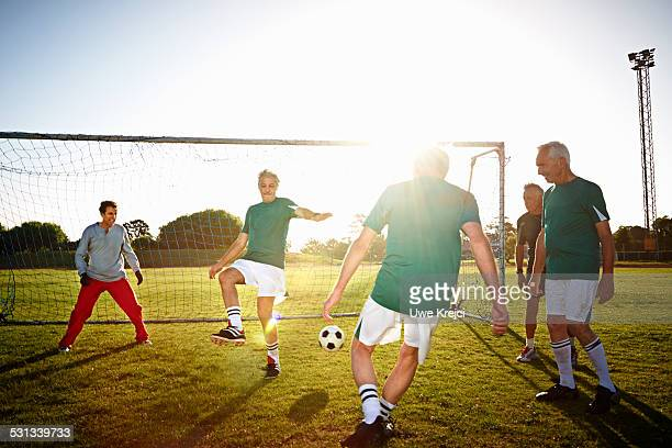 mature men playing soccer on sports field - defender soccer player stock pictures, royalty-free photos & images