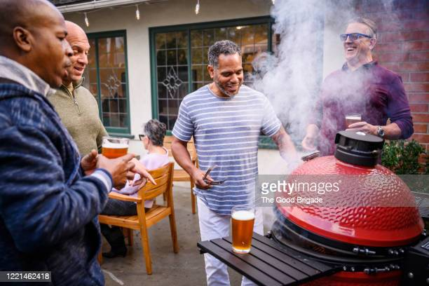 mature men standing by barbecue grill talking - men friends beer outside stock pictures, royalty-free photos & images