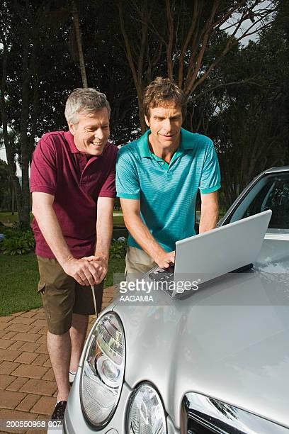Mature men using laptop at golf clubs parking lot