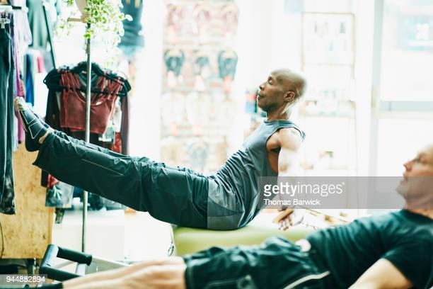 Mature men using pilates reformer while exercising during class in fitness studio